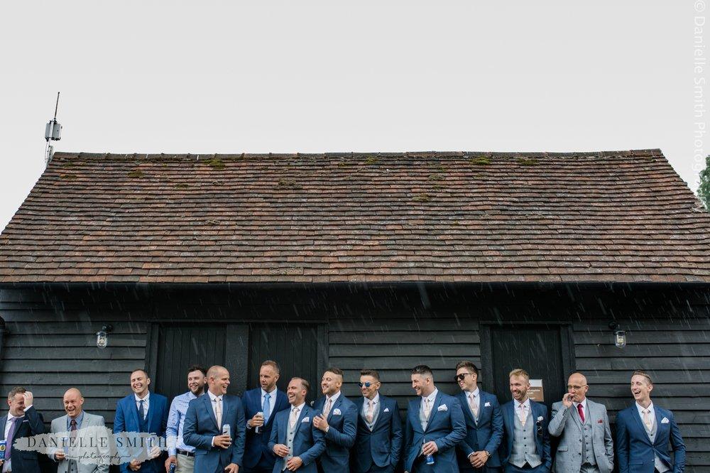 groom and groomsmen in the rain at blake hall wedding venue