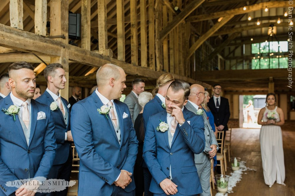 groom crying as bride walks down the aisle