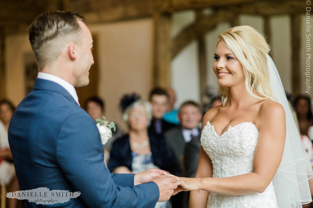 bride and groom holding hands during ceremony - blake hall wedding photography