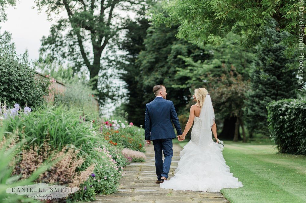 newly weds walking in the gardens at blake hall