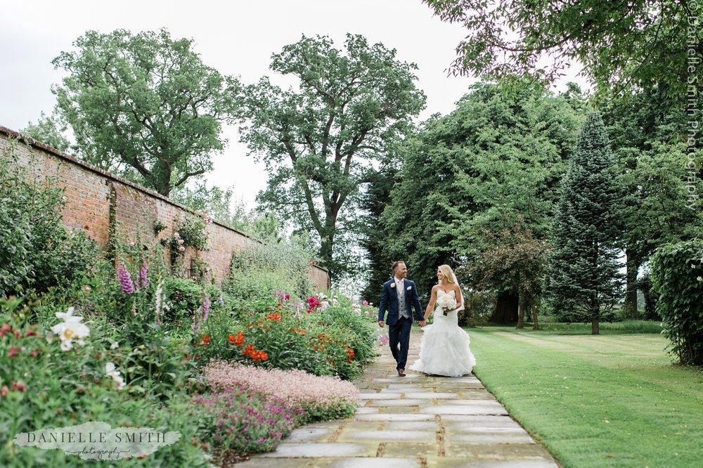 blame hall gardens - bride and groom walking