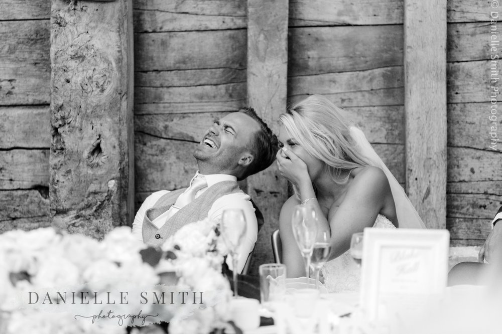 bride and groom laughing during the speeches at the wedding bride and groom laughing - blake hall wedding photography