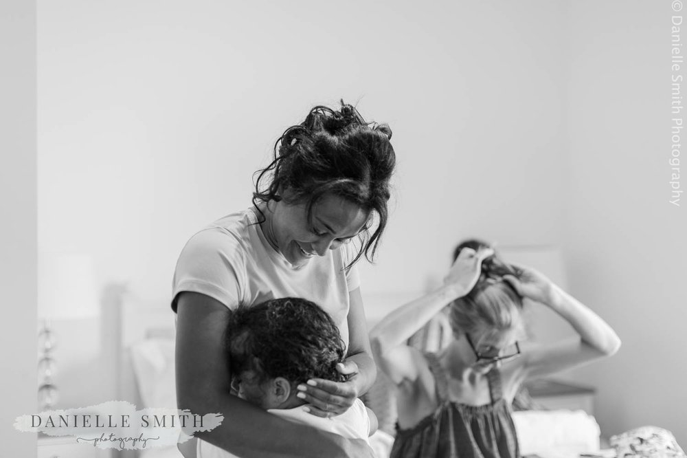 bride hugging her daughter on morning of wedding