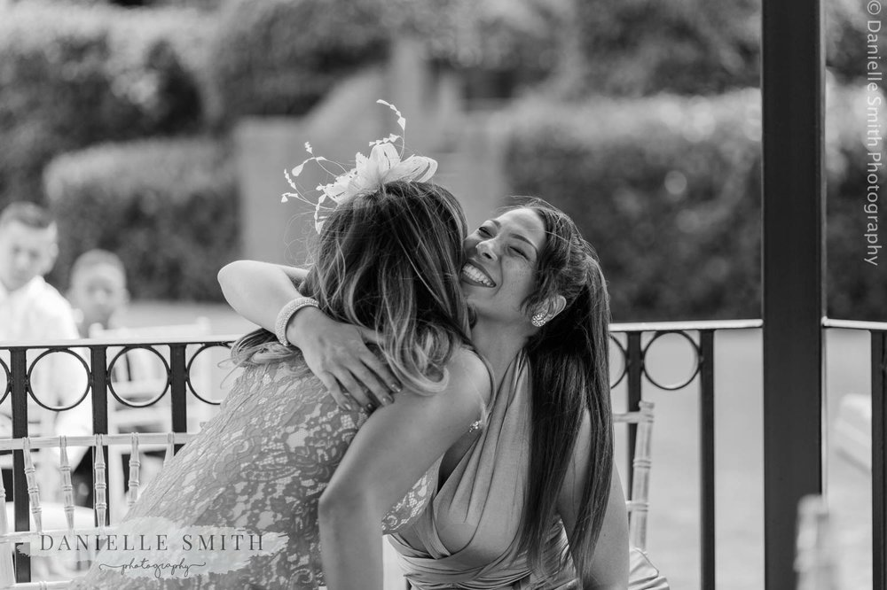 ladies hugging at outdoor wedding ceremony