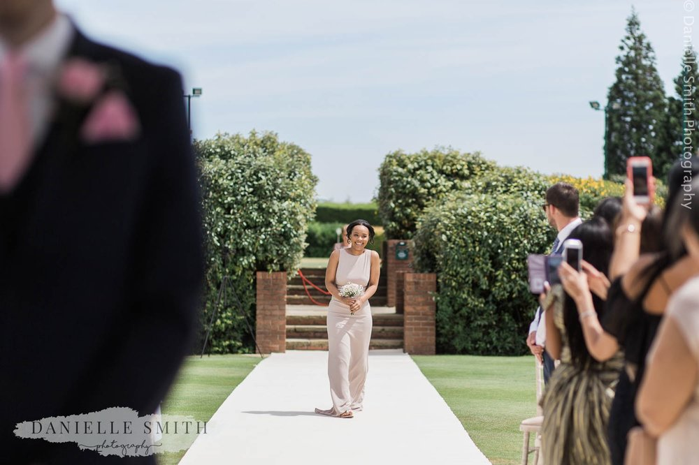 bridesmaid walking down aisle at outdoor wedding in billericay