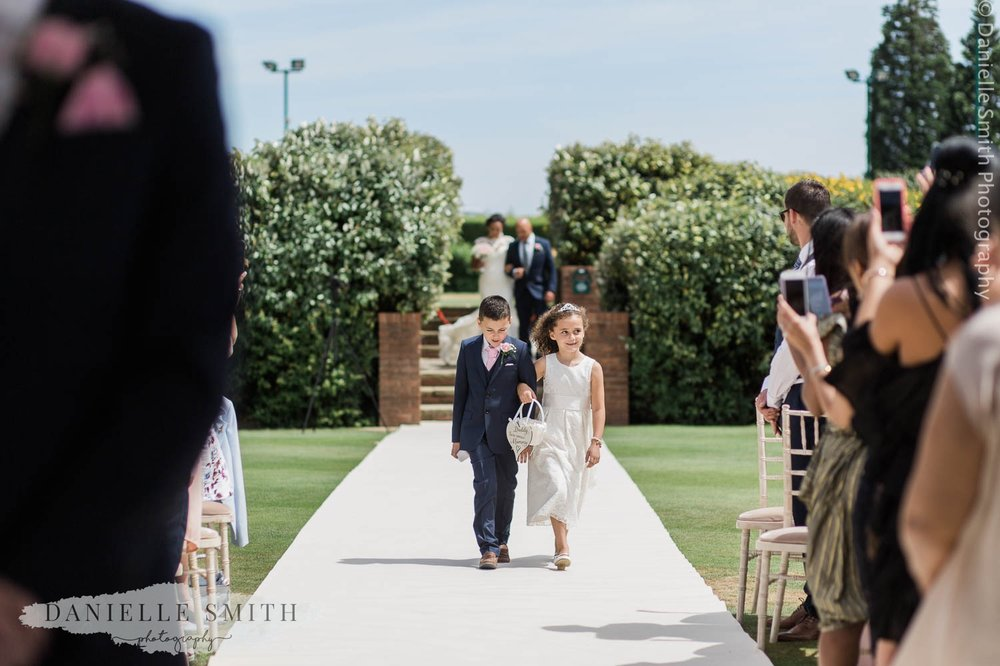 page boy and flower girl walking down aisle at stock brook manor