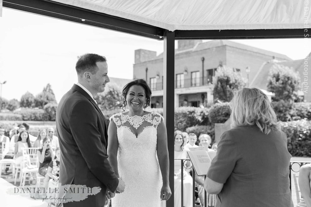 bride and groom smiling during outdoor ceremony