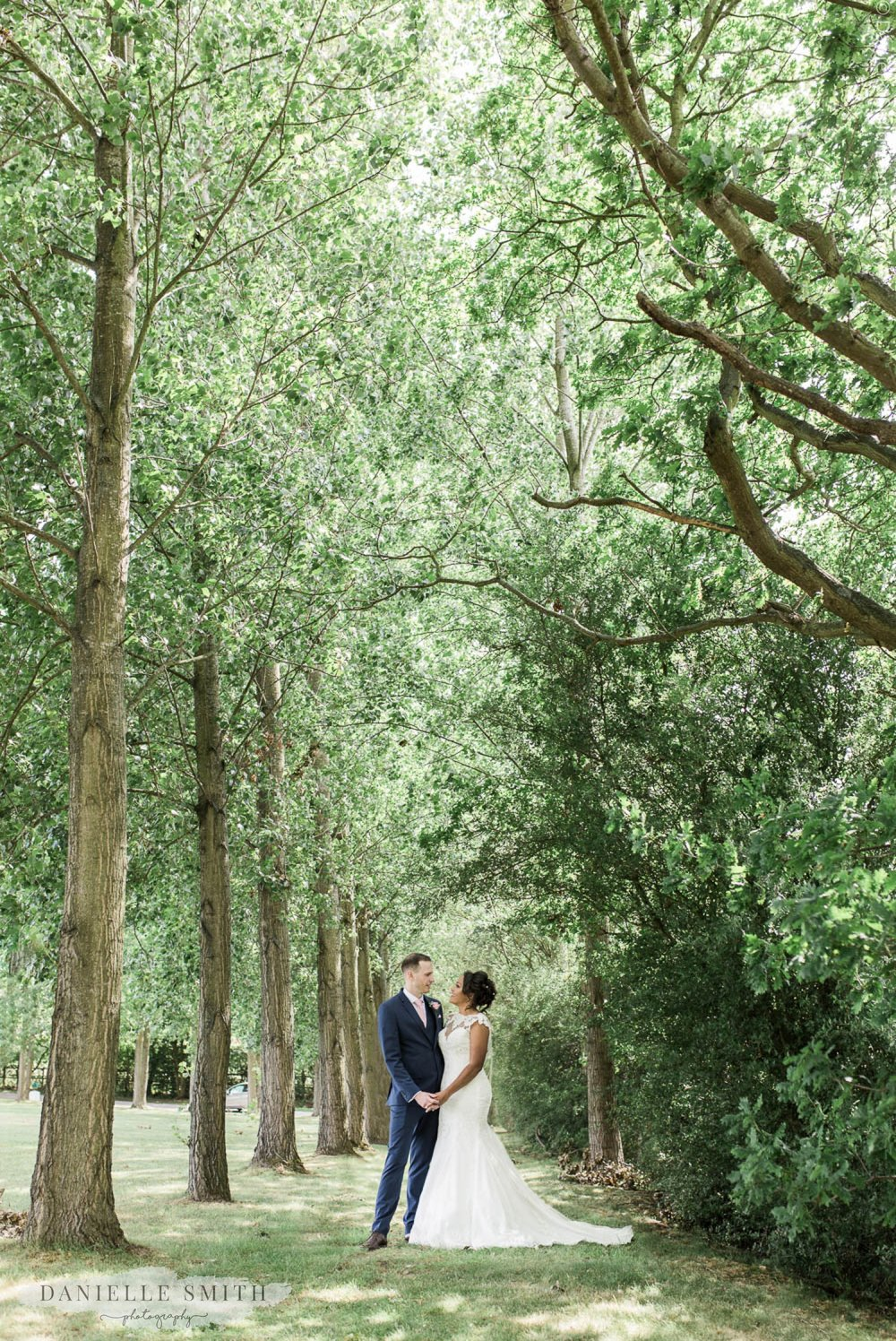 bride and groom between trees