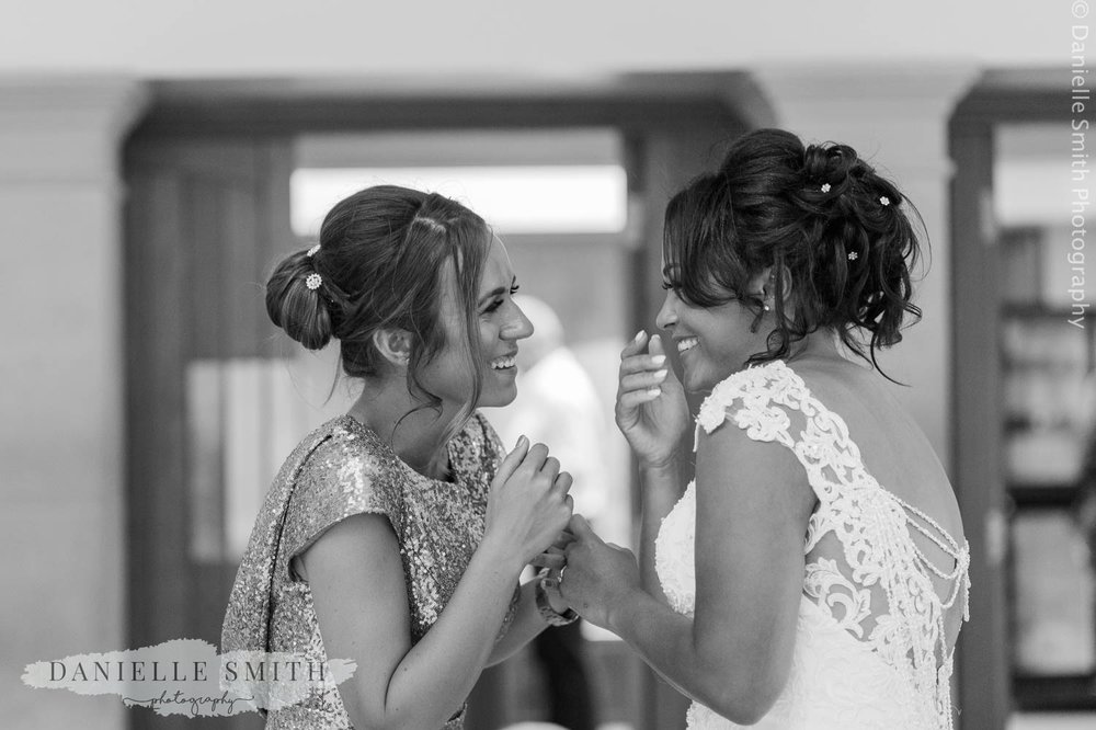 bride and her friend laughing during evening