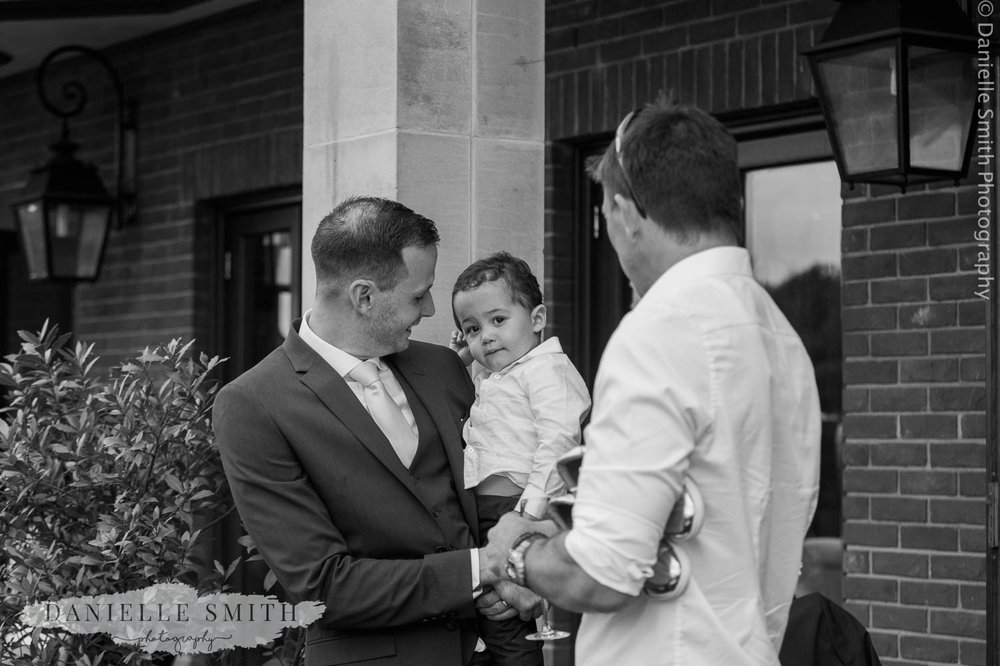groom holding son at wedding