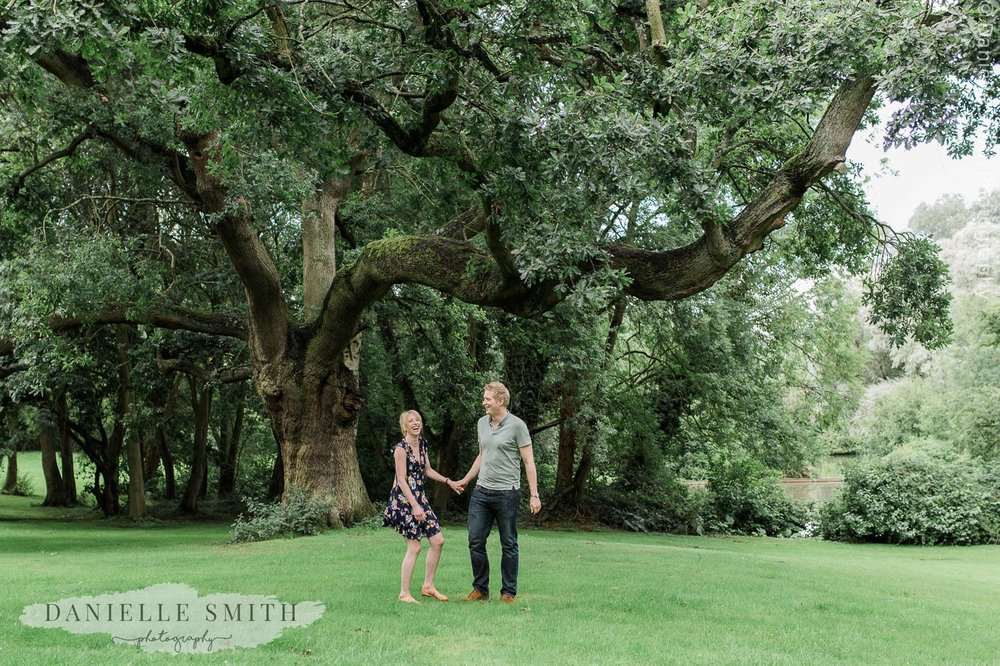 couple laughing by tree - little easton pre-wedding photography