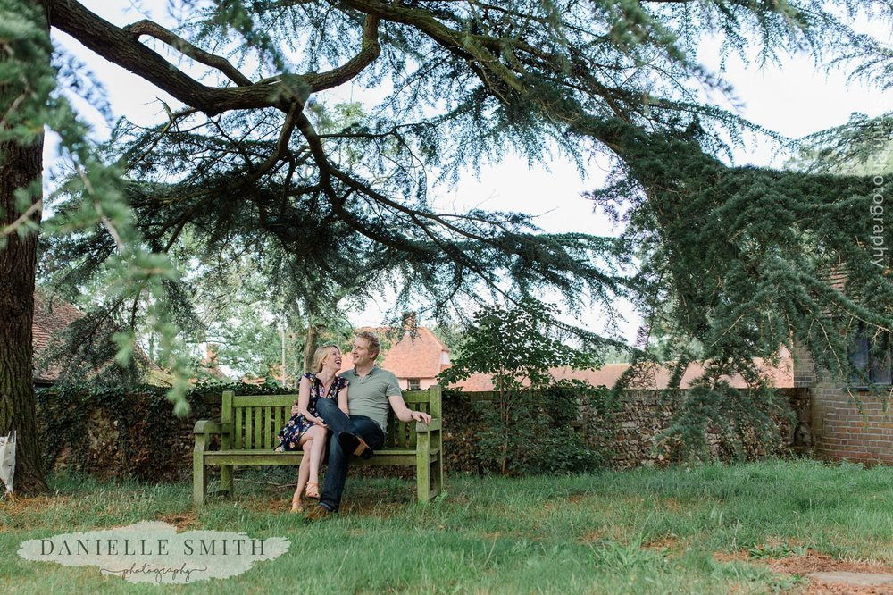 couple sitting on bench at little easton church