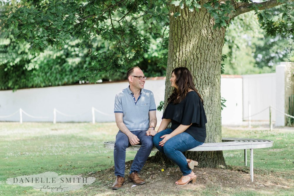 couple sitting on bench - stock village engagement session