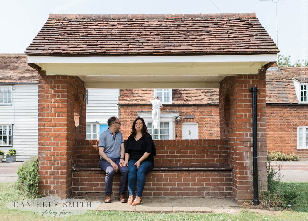 couple sitting at brick bus stop - stock village engagement session