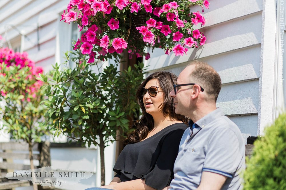 couple sitting outside pub with flowers in Stock village