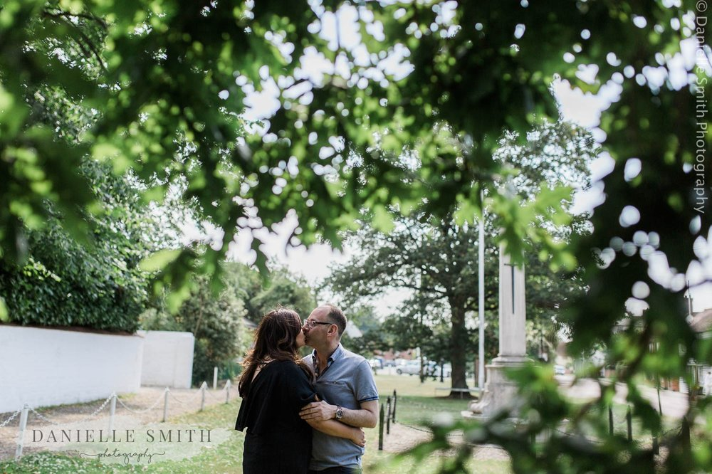 couple kissing under tree in stock