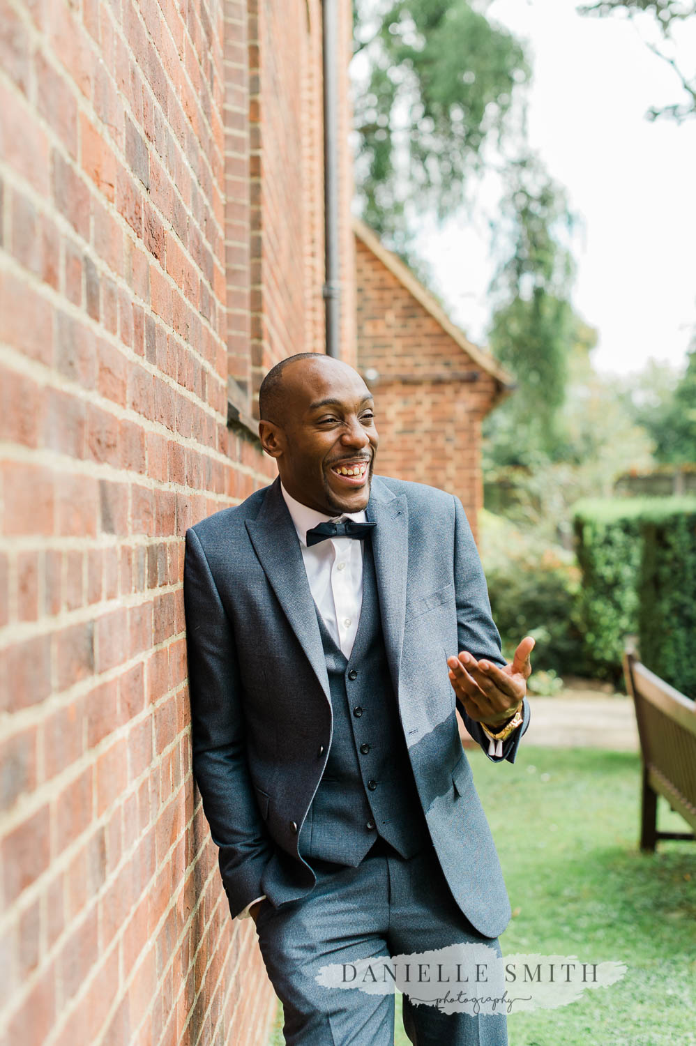 groom outside church laughing - laid back wedding