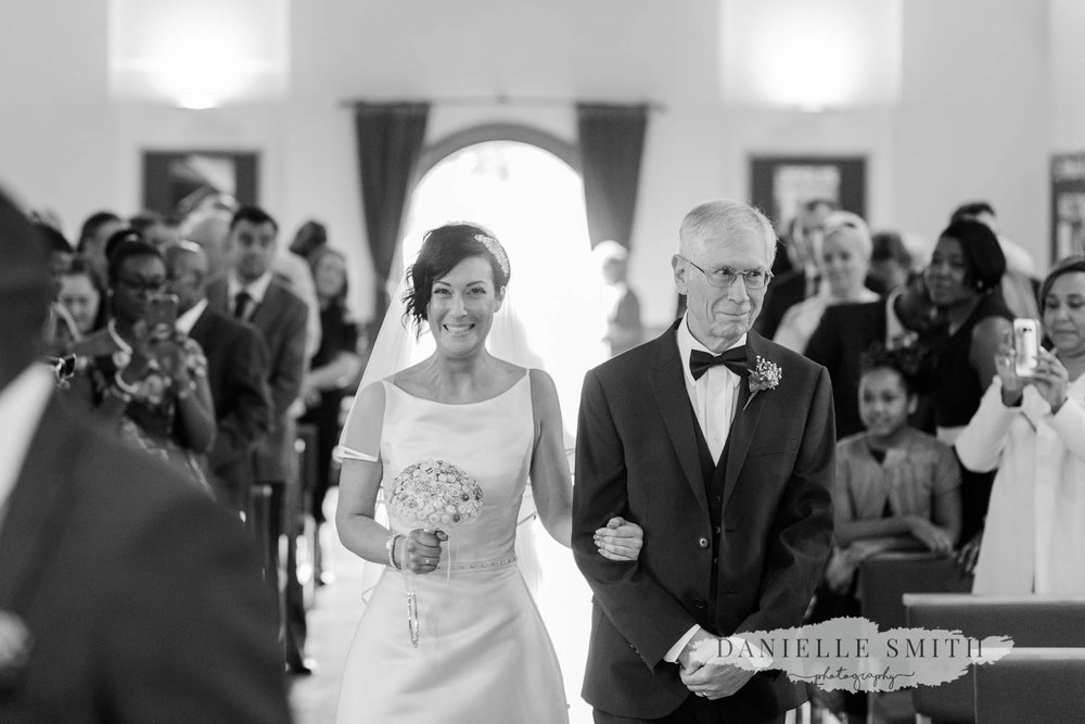 bride excited as she walks down aside with dad