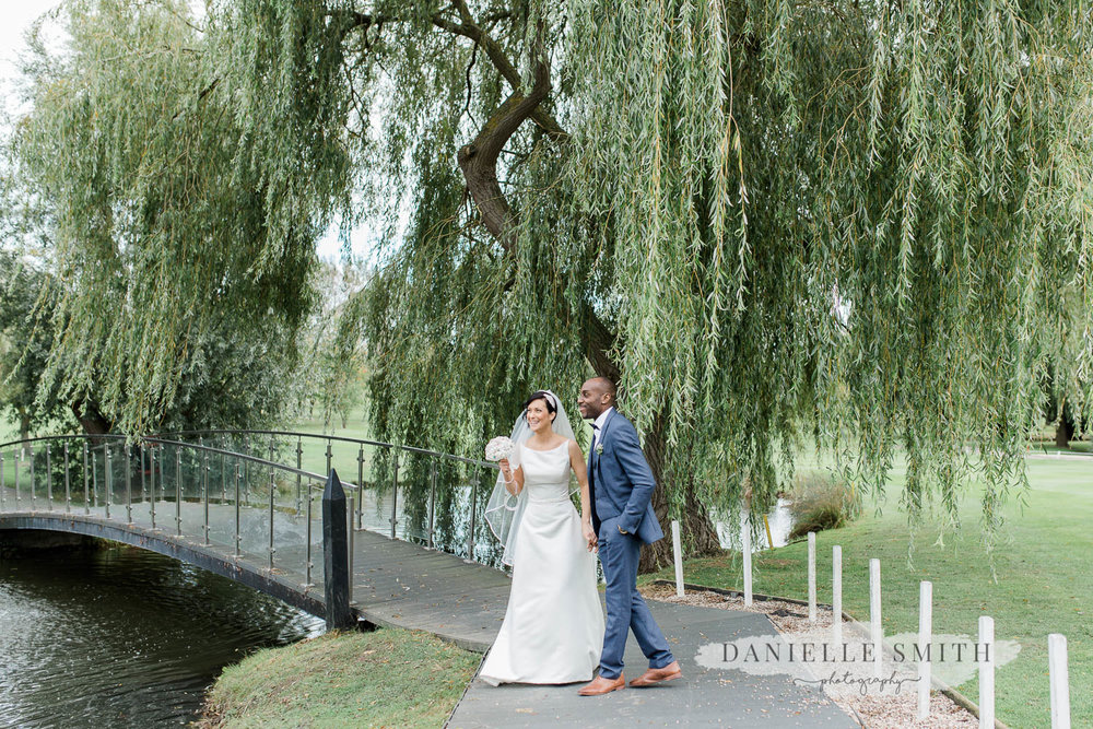 bride and groom with bridge and willow tree