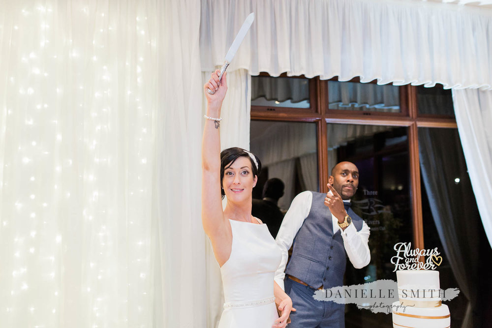bride holding knife up for cake cut