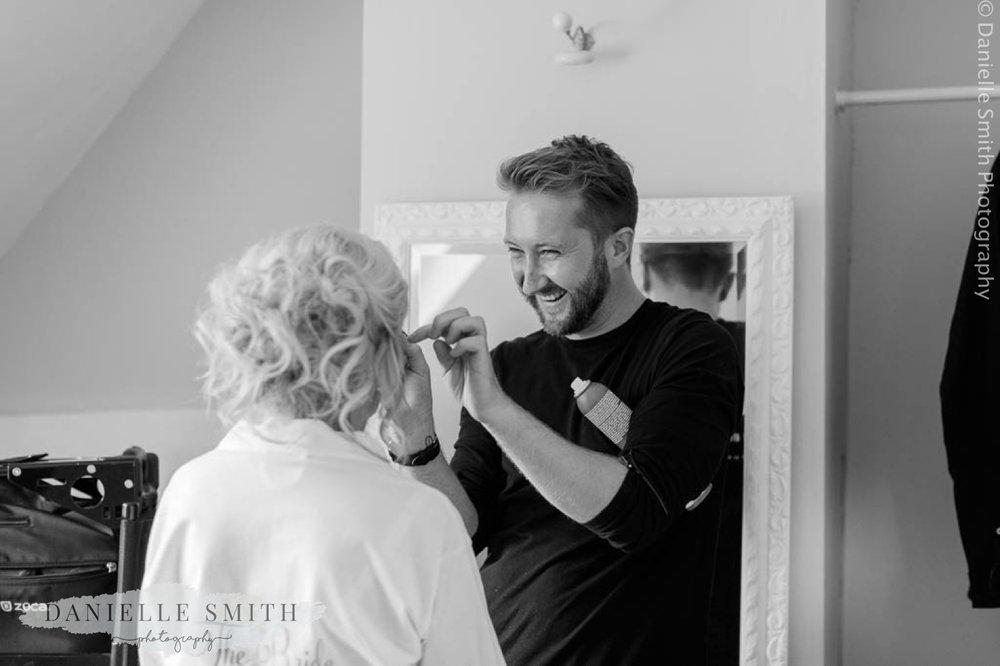 hair dresser laughing while doing brides hair