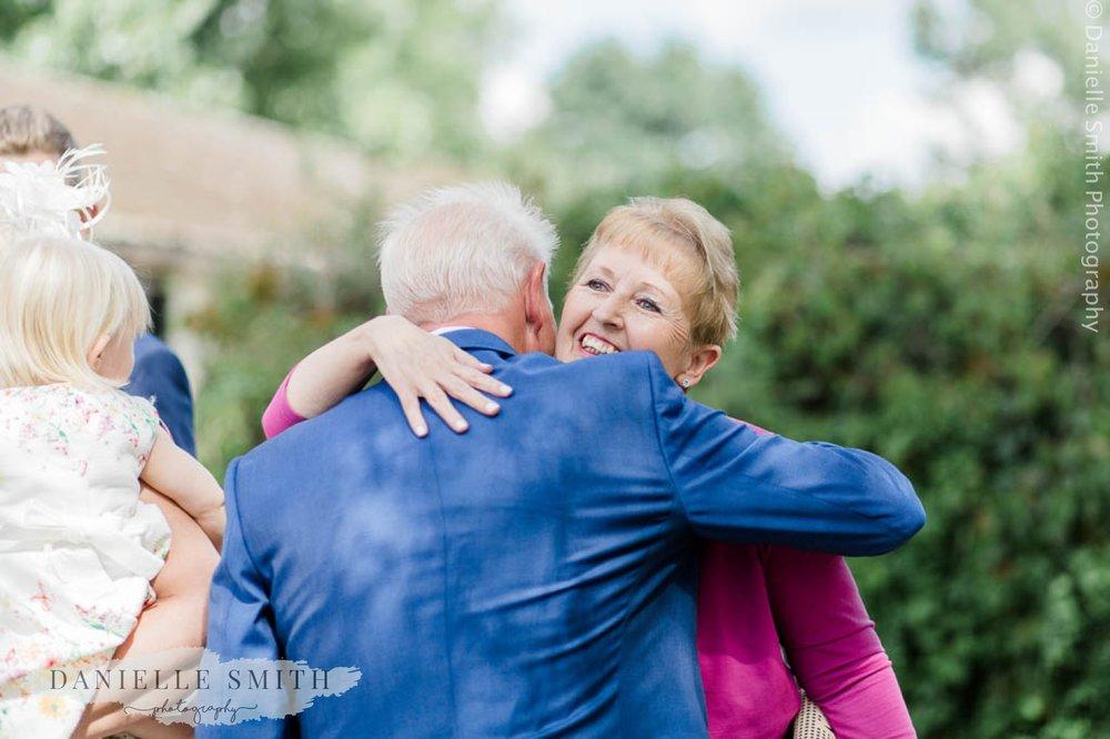 groom hugging wedding guest