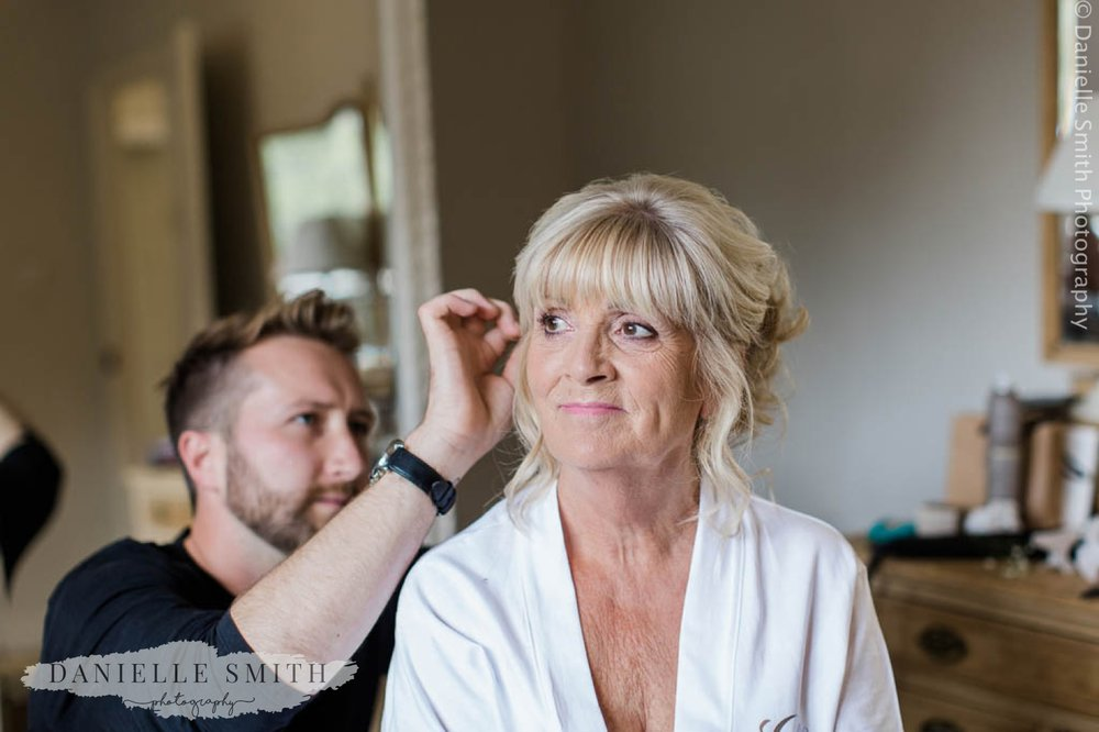 bride having finishing touches to hair