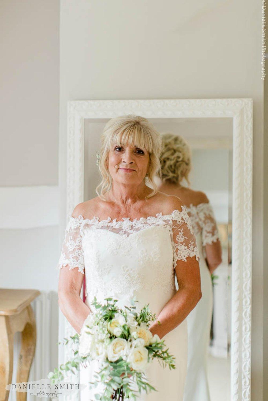 older bride holding ivory bouquet