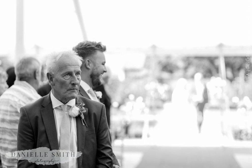 groom looking worried as waits for bride