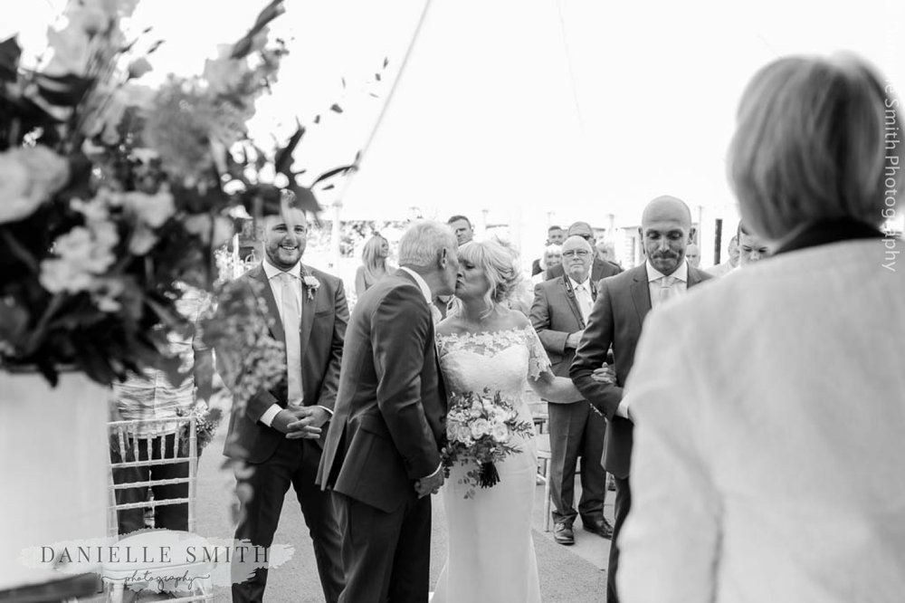 groom kissing his bride as she arrives
