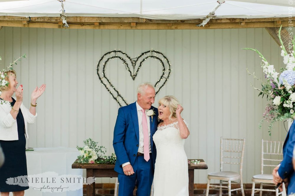 bride and groom cheering after married - houchins wedding photographer