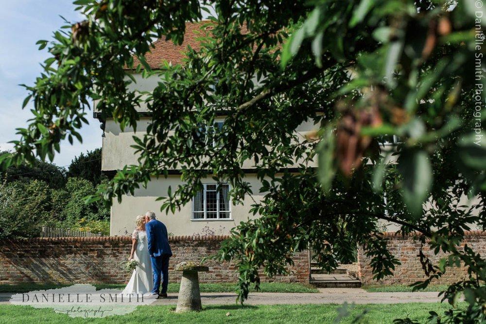 bride and groom kissing outside houchins farm house