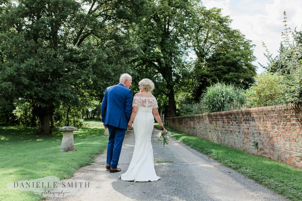 bride and groom walking down path - houchins wedding photography