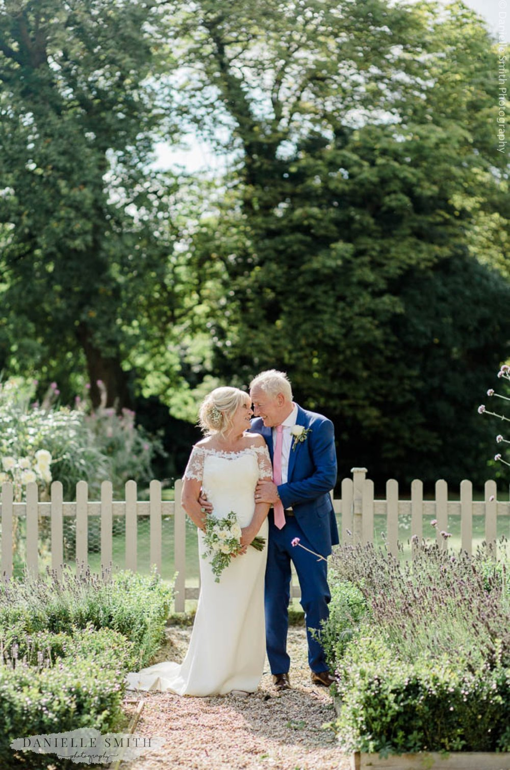 brid and groom looking at each other in gardens