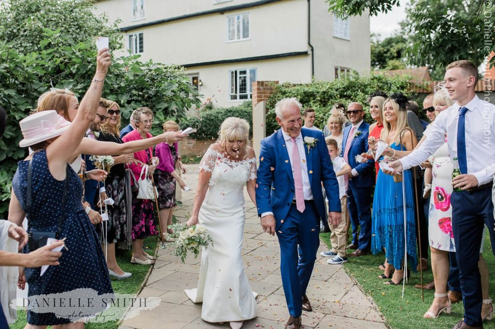 guests throwing confetti over bride and groom - houchins wedding