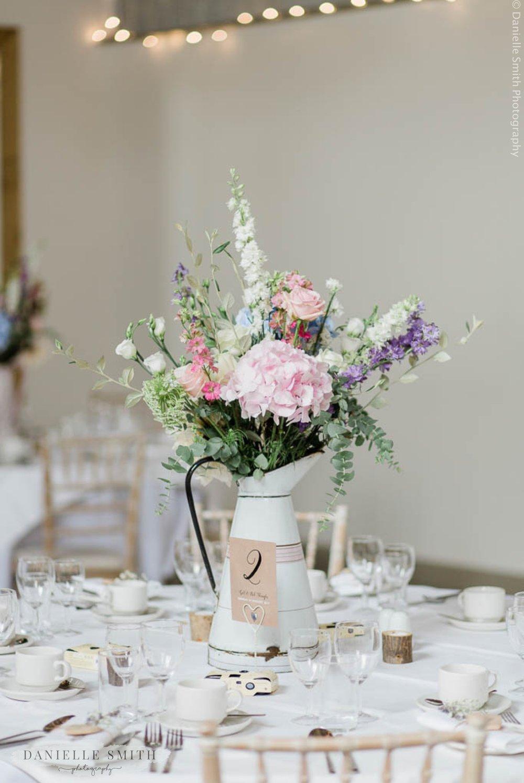 pastel flowers in jug on wedding table