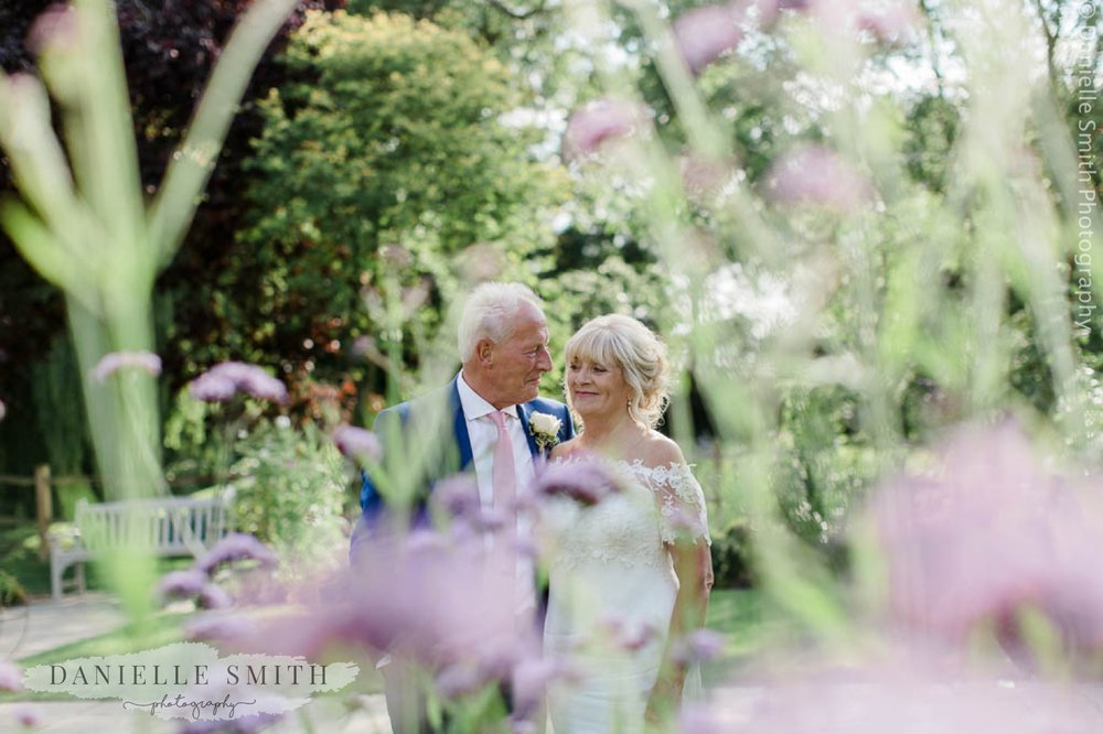 bride and groom smiling through flowers