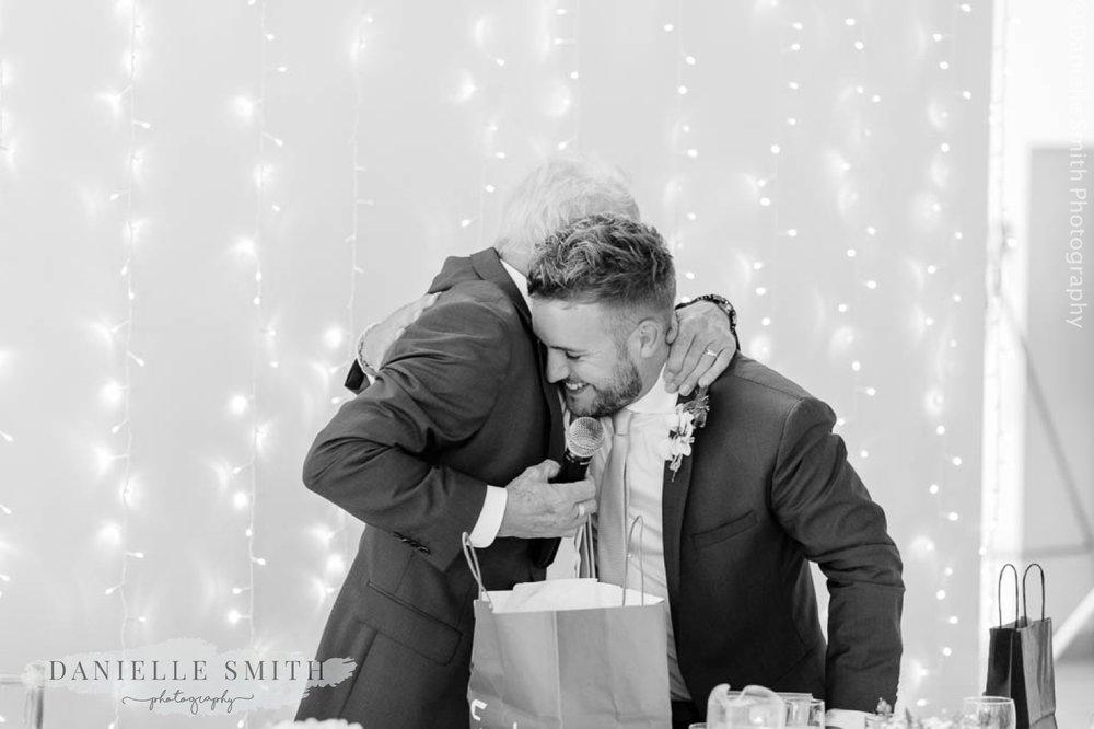 groom hugging his son after speech