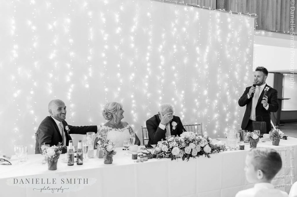 groom embarrassed and top table laughing - houchins wedding