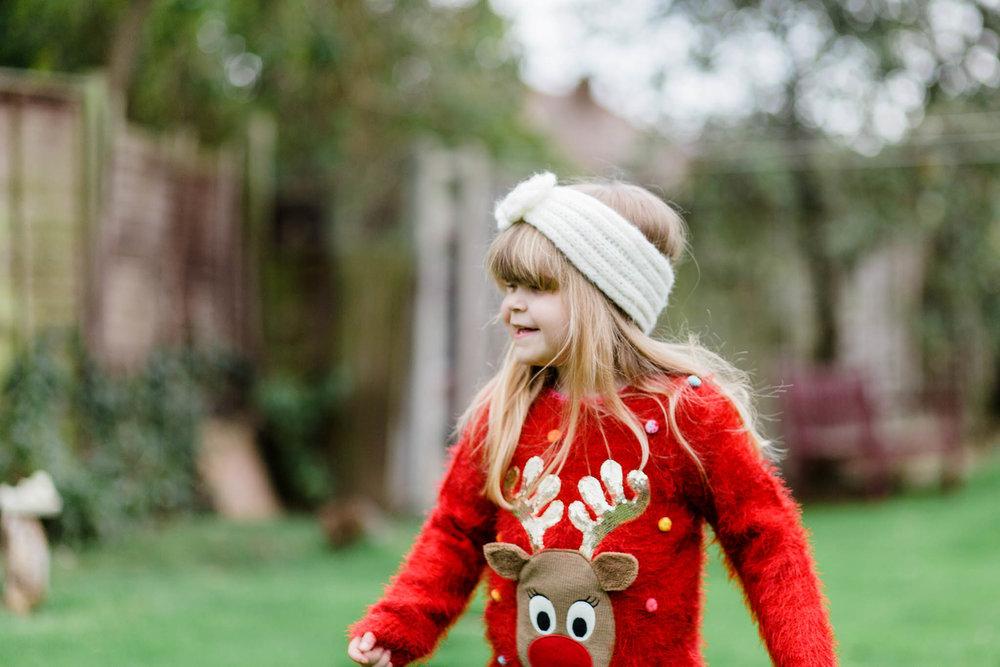little girl wearing reindeer xmas jumper