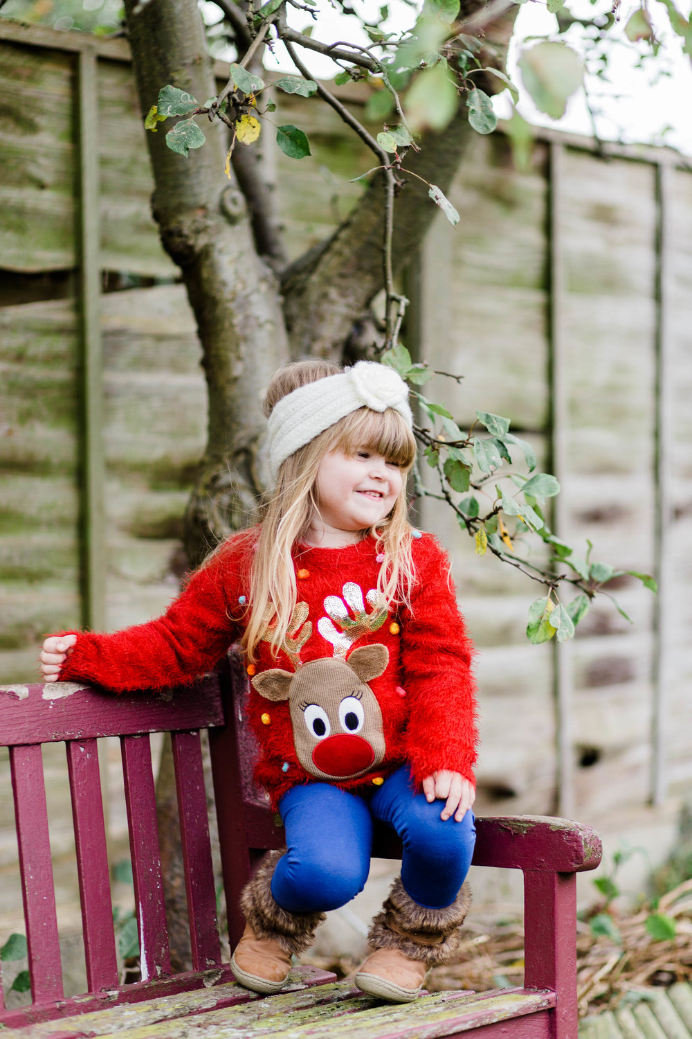 little girl laughing on bench in christmas jumper