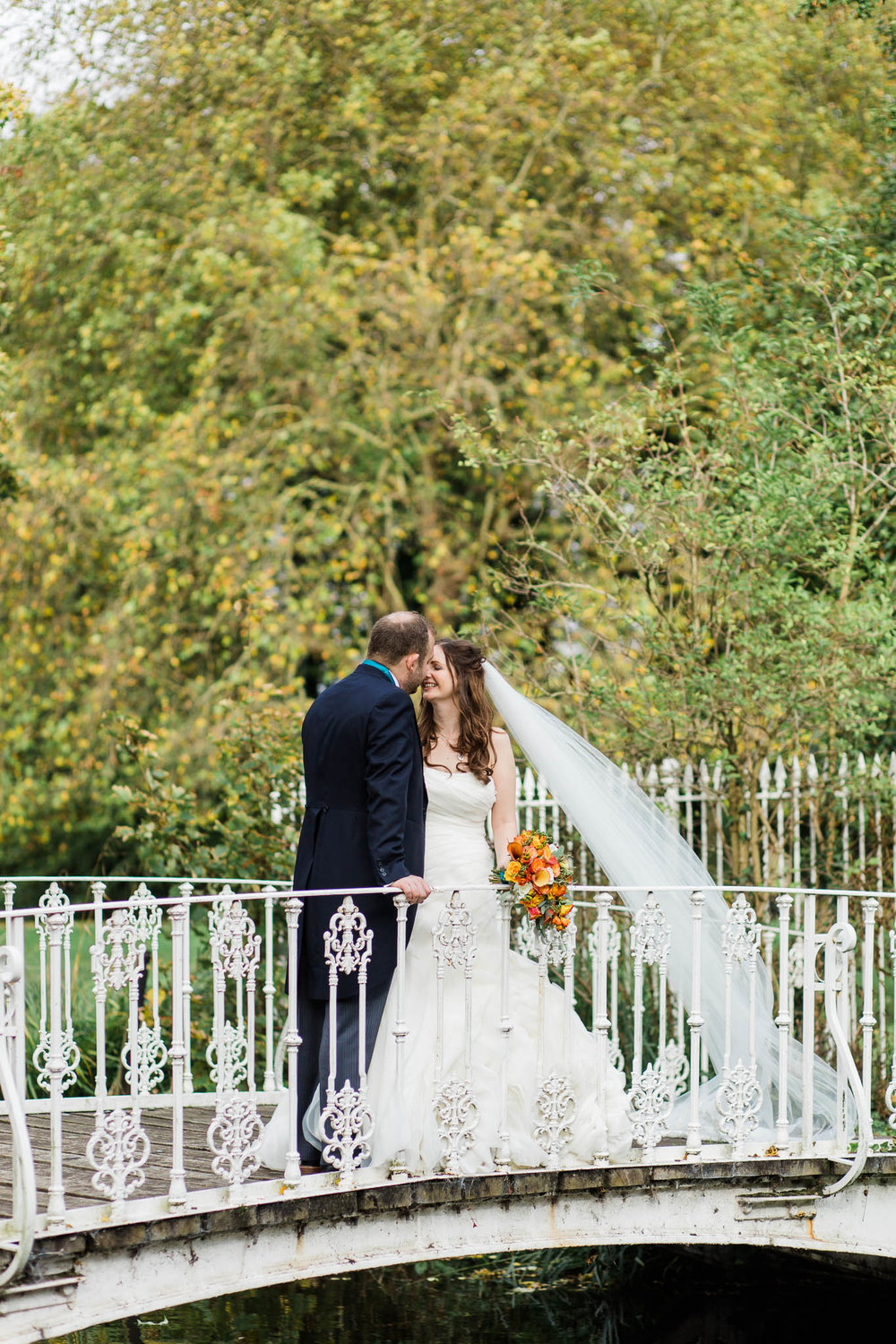 bride and groom on bridge - morden hall wedding