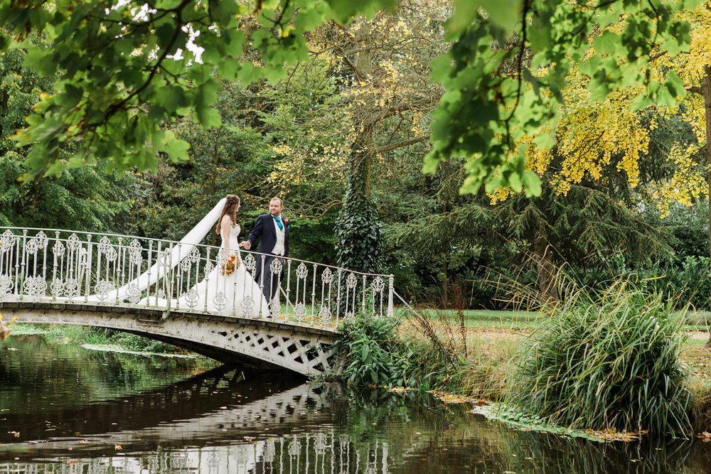 bride and groom walking over bridge - autumn wedding