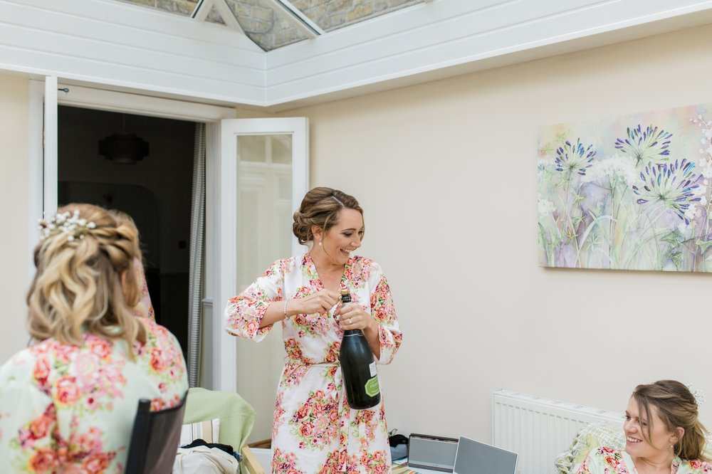 bride popping champagne in her robe