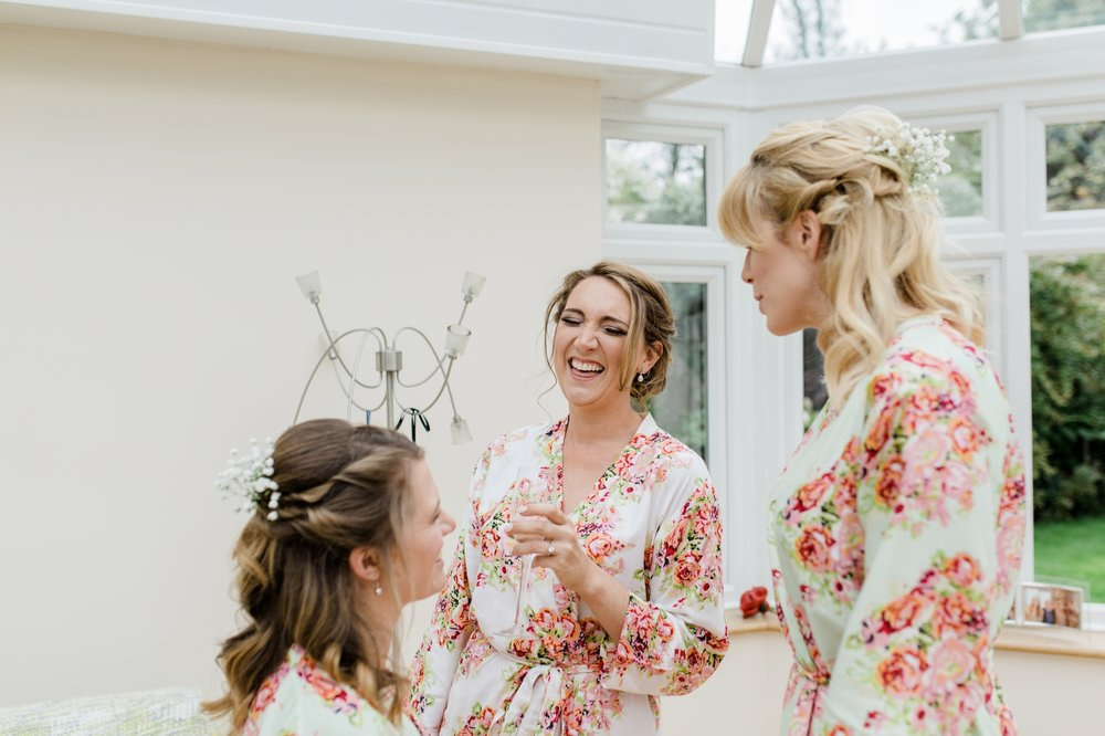 bride laughing with floral robe on