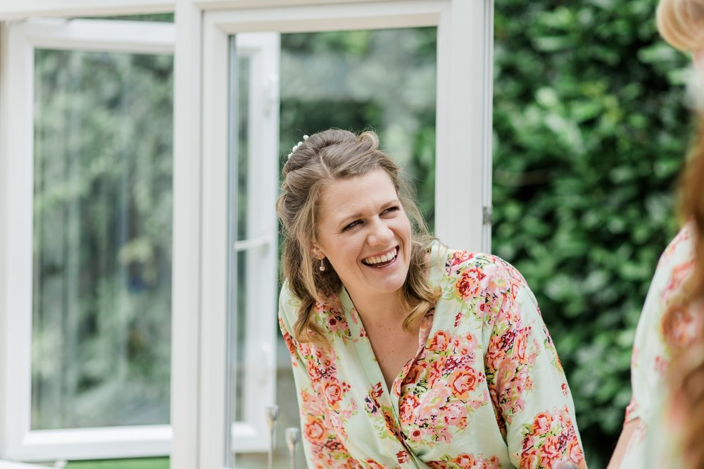bridesmaid laughing with floral robe on - relaxed marquee wedding