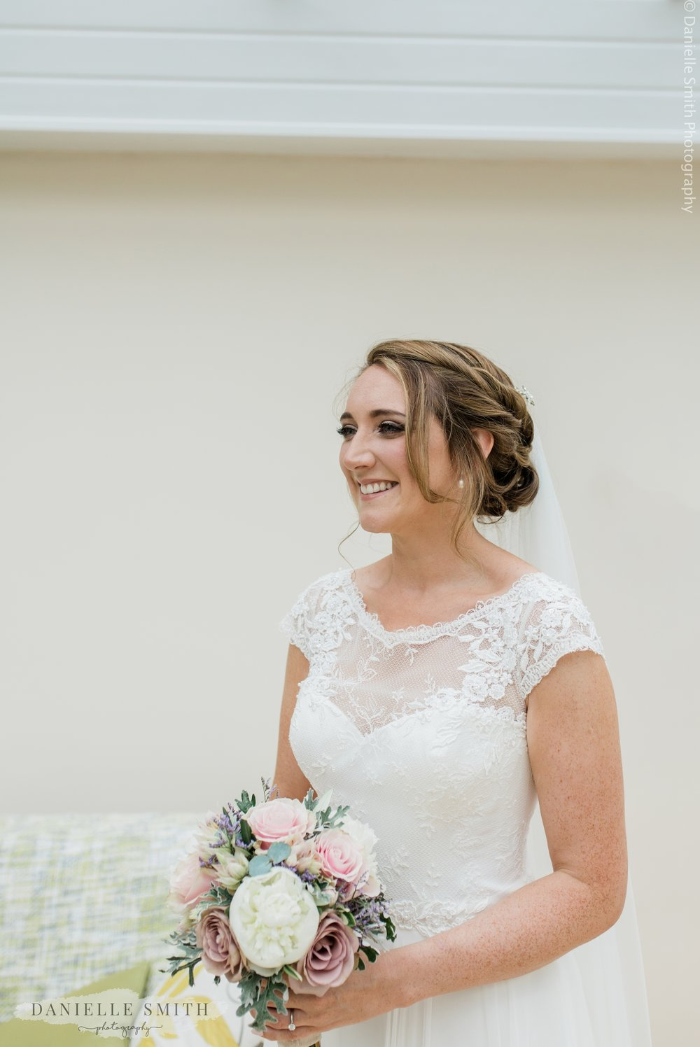 beautiful bride holding pastel coloured bouquet - relaxed marquee wedding