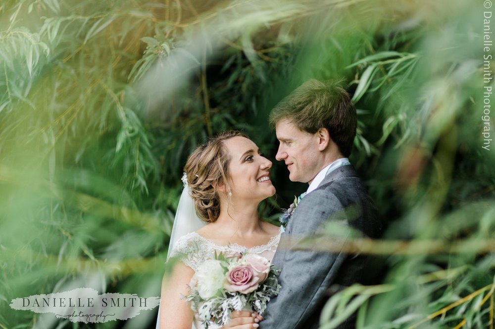 bride and groom through bushes