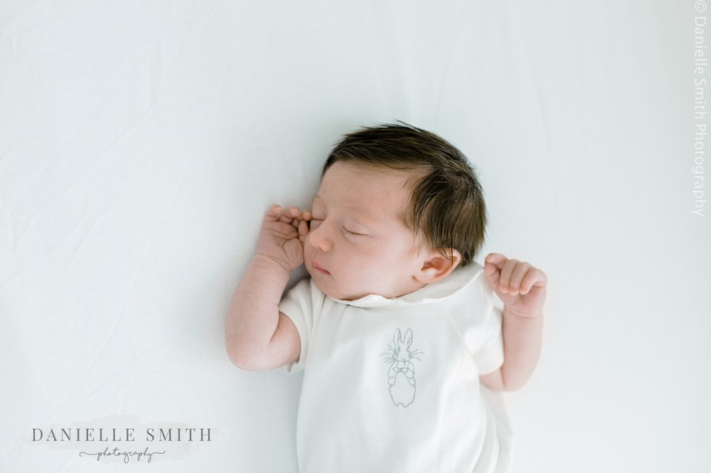 baby girl asleep in cot - natural newborn baby photos at home