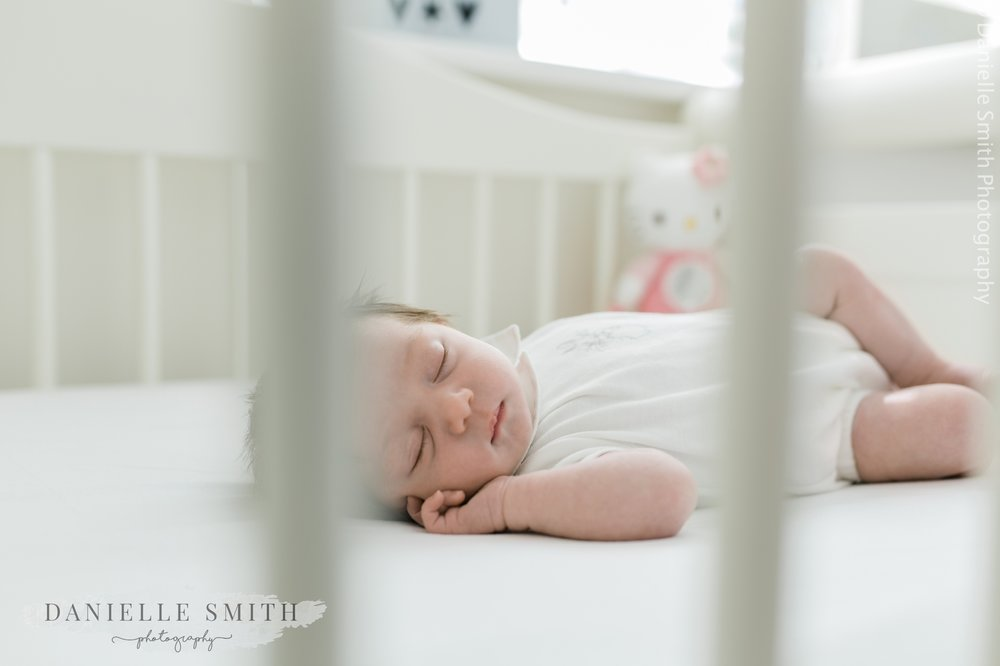 newborn baby girl asleep in cot